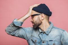 Sideways portrait of bearded male has regretful expression, keep. S hand on forehead, looks desperately, isolated over pink background. Stressful unshaven man in royalty free stock photos