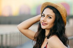 Sideways portrait of brunette female with dark eyes, red lips and healthy pure skin wearing straw hat smiling pleasantly at camera. Having happy expression royalty free stock photography