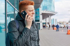 A sideways portrait of fashionable boy with trendy hairdo red hair wearing stylish jacket holding rucksack on his back communicati Royalty Free Stock Images