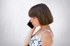 Sideways portrait of little girl with bobbed hair, wearing white dress, speaking over cell phone with serious expression. Stylish. Female kid posing in studio stock images