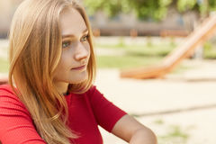 Sideways portrait of pretty young student girl with fair hair, charming eyes and freckles looking pensively into distance thinking Stock Photography