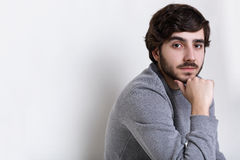 Sideways portrait of young hipster having dark beard with moustache big dark eyes, thick eyebrows and fashionable hairstyle holdin Stock Images