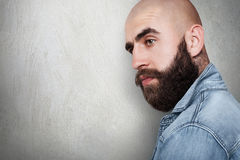A sideways portraitwith copy space of fashionable bald hipster having tattoo on his neck, thick black eyebrows and beard, big dark. Eyes wearing jean shirt stock photo