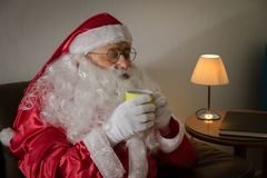 Sideways of Santa Claus relaxing in sofa at home enjoying a cup. Sideways of Santa Claus or Kris Kringle relaxing in sofa at home enjoying a cup of coffee or tea stock photography