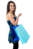 Sideways of shopping teen girl. Trendy girl with polka dots shopping bags Royalty Free Stock Images