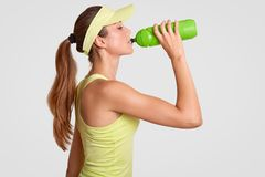 Sideways shot of exhausted tennis player drinks water as feels thirrsty after active game, has fit body shape, dressed casually, i royalty free stock photography