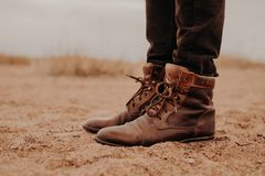 Sideways shot of man in shaggy brown shoes on lay surface. Pair of boots on sand. Male has outdoor walk in old footwear stock photography