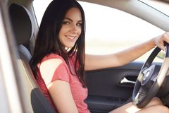 Sideways shot of pleasant looking brunette woman sits in her own automobile, keeps hands on wheel, enjoys high speed, dressed in c royalty free stock photos