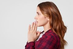 Sideways shot of pretty female keeps hands in praying gesture, wears checkered shirt, poses over white background with free space. Believes in good fortune stock photography
