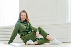 Sideways shot of satisfied redhead woman has makeup, wears tracksuit, white spotshoes, rests on floor, does stretching exercises,. Is fond of sport. People stock photos