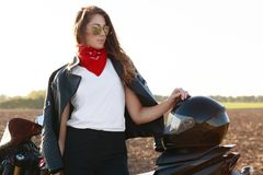 Sideways shot of thoughtful brunette woman wears stylish leather jacket, trendy shades, stands near motorbike, keeps hand on helme royalty free stock photos