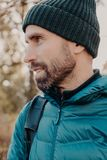 Sideways shot of unshaven man with dark thick beard, wears warm har and anorak, looks pensively aside, poses outside, dreams about. Something has outdoor stroll stock photos