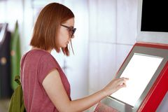 Sideways shot of young Caucasian female with bobbed hairstyle, wears trendy shades, uses ATM machine for withdrawing money, stock photography