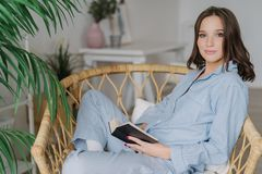 Sideways shot of young female reader hold book in hands, rests at home, wears pyjamas, enjoys calm atmosphere, reading bestseller,. Sits in wicker chair. People stock photography