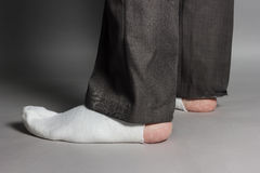 Sideways standing feet with white socks and a big hole in front. Of grey background royalty free stock image