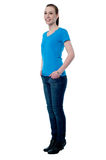 Sideways of young female. Pretty woman with hands in her pockets Stock Photo
