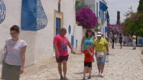 Sidi Bou Said, Tunísia - 6 de junho de 2018: Povos felizes do turista que andam na rua da cidade antiga na estância turística Mul filme