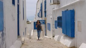 Sidi Bou Said, Tunisia - 06 June 2018: Adult woman walking on narrow street in old city and eating ice cream. Tourist stock video