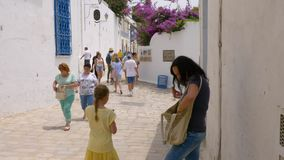 Sidi Bou Said, Tunisia - 06 June 2018: Crowd of tourists people walking on narrow street in resort town. Travelling stock video footage