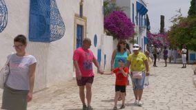 Sidi Bou Said, Tunisia - 06 June 2018: Happy tourist people walking on ancient city street in resort town. Crowd of stock footage
