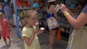 Sidi Bou Said, Tunisia - 06 June 2018: Tourist people choose sweet snacks in candy store. Girl teenager eating ice cream. In sweet shop while travel stock video