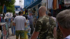 Sidi Bou Said, Tunisia - 06 June 2018: tourist people choosing souvenirs and gifts on local market. Tourists people stock video