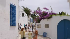 Sidi Bou Said, Tunisia - 06 June 2018: Tourists people walking on ancient street in old city. Traveling people on narrow stock footage