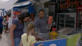 Sidi Bou Said, Tunisia - 06 June 2018: Young mother and daughter buying ice cream in candy shop while walking on resort stock video footage