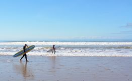 Two surfers carrying a surfboard on the beach near Essaouira Stock Photo