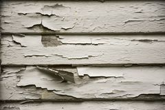 OLD PEELING CRACKED WHITE PAINT ON WOOD SIDING. The siding of a house shows the peeling and cracked white paint that shows the need for a new coat royalty free stock photography