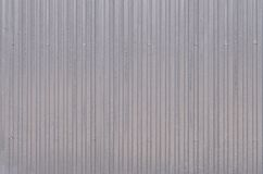 Siding, metal panels texture closeup in the daytime outdoors. Metal wall or fence embossed metal sheets. Terrain and large metal sheet as a barrier or fence Royalty Free Stock Photo