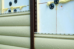Siding panels mounting over insulation on building wall in rainy day Stock Image