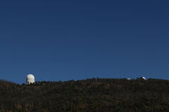Siding Springs Telescope. Image shows the Siding Springs Telescope near Coonabarabran, NSW, Australia as a silhouette along the ridge with two smaller telescopes Royalty Free Stock Photos