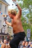 SIDMOUTH, ДЕВОН, АНГЛИЯ - 5-ОЕ АВГУСТА 2012: Juggler улицы принимает рукоплескание от благодарной толпы после использования пылат стоковое изображение rf