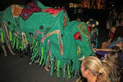 SIDMOUTH, DEVON, ENGLAND - AUGUST 10TH 2012: A green chinese dragon gets stroked by spectators as it takes part in the night time. Closing procession of folk royalty free stock photo