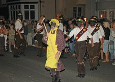 SIDMOUTH, DEVON, ENGLAND - AUGUST 10TH 2012: A troup of traditional English Morris dancers led by a man with a broom and a yellow stock image