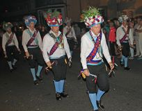 SIDMOUTH, DEVON, ENGLAND - AUGUST 10TH 2012: A troup of traditional English Morris dancers takes part in the night time closing. Procession of folk week stock photo