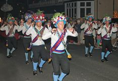 SIDMOUTH, DEVON, ENGLAND - AUGUST 10TH 2012: A troup of traditional English Morris dancers takes part in the night time closing. Procession of folk week stock photos