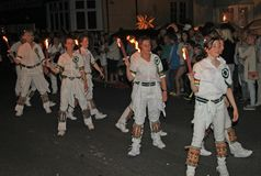 SIDMOUTH, DEVON, ENGLAND - AUGUST 10TH 2012: A troup of young lady Morris dancers hold their flaming torches as they takes part in stock photo