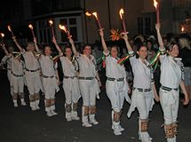 SIDMOUTH, DEVON, ENGLAND - AUGUST 10TH 2012: A troup of young lady Morris dancers hold their flaming torches high as they takes stock photography