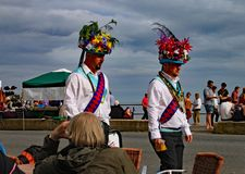 SIDMOUTH, DEVON, ENGLAND - AUGUST 8TH 2012: Two Morris dancers in extravagant head gear walk along the Esplanade during folk week royalty free stock images