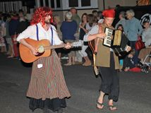 SIDMOUTH, DEVON, ENGLAND - AUGUST 10TH 2012: Two performers in fancy dress play a guitar and an accordian in the night time. Closing procession of folk week royalty free stock images