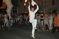 SIDMOUTH, DEVON, ENGLAND - AUGUST 10TH 2012: A very energetic young man dressed all in white and holding a cloth and a flaming. Torch, dances along in the night stock photo