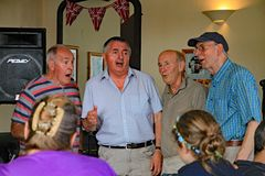 SIDMOUTH, DEVON, ENGLAND - 5. AUGUST 2012: Vier reifere Sänger führen acapella an einer öffentlichen Mikrofonsitzung in einer See lizenzfreies stockfoto