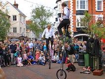 SIDMOUTH, DEVON, ENGLAND - 5. AUGUST 2012: Zwei Straßenjongleure und -entertainer führen im Marktplatz zu einem anerkennenden dur lizenzfreies stockfoto