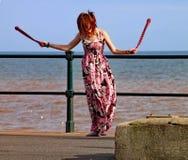 SIDMOUTH DEVON, ENGLAND - AUGUSTI 5TH 2012: En ung kvinna underhåller förbipasserande förbi med att snurra klubbor vid järnräcken royaltyfri fotografi