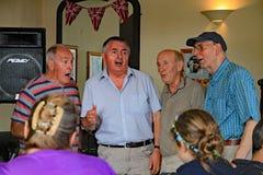 SIDMOUTH DEVON, ENGLAND - AUGUSTI 5TH 2012: Fyra mognare sångare utför acapella på en öppen mikrofonperiod i en bar för havsframd royaltyfri foto
