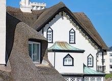SIDMOUTH, DEVON - 1ER AVRIL 2012 : La belle vieille résidence couverte de chaume se tient sur la côte de Sidmouth un jour ensolei images stock