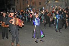 SIDMOUTH, DEVON, INGHILTERRA - 10 AGOSTO 2012: Un gruppo di musicisti e di ballerini dell'impedimento vestiti nel malva e nel ver fotografia stock libera da diritti