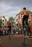 SIDMOUTH, DEVON, INGLATERRA - 5 DE AGOSTO DE 2012: Dois jugglers e anfitriões da rua executam com os unicycles e os clubes do fog fotos de stock